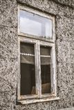 Broken window. Of an abandoned house, with naked walls no plasterwork, the devastated interior visible royalty free stock image