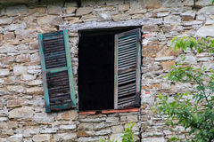Broken window with green wooden shutter in a stone wall l of an Stock Photography