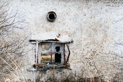 A broken window on an old house. Dirty gray, damaged wall Stock Images