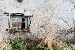 A broken window on an old house. Dirty gray, damaged wall Stock Photography