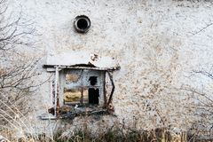 A broken window on an old house. Dirty gray, damaged wall Stock Image