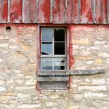 Broken Window on Old Vintage Barn. A broken window framed in weathered wood is centered on an old barn building Stock Photography