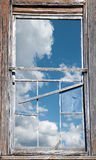 Broken Window with Sunny Sky. Weathered wood siding and sashes frame a broken and deteriorating 12 pane window. Through the window, one can see a clear royalty free stock photos