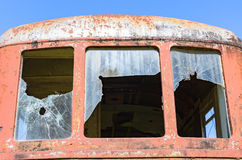 Broken window of a train. Broken window of a red rusted train, abandoned train royalty free stock photography