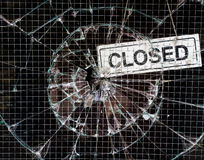 Broken Window Vandalism - Shop Closed. Hole smashed in the reinforced glass of a vandalised shop window, with a sign saying the shop is closed royalty free stock photos
