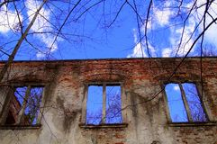 Broken window in a wall. Broken windows in a old wall of the collapsed house looking on blue sky and trees, broken old life with a hope, Discarded ruin with old Royalty Free Stock Image