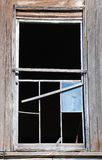 Broken Window. Weathered wood siding and sashes frame a broken and deteriorating 12 pane window Stock Images