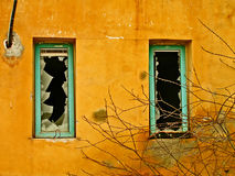 Broken windows. Old orange house walls with broken windows Stock Photo