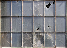 Broken windows. Reinforced glass holds together as best as possible at an industrial building destined to become lofts Royalty Free Stock Photography