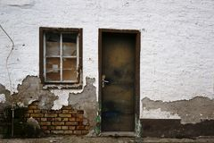 Dilapidated residential building. Broken windows and the crooked door of a dilapidated residential building Stock Photos