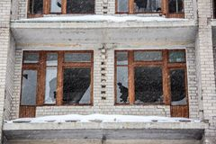 Broken windows of destroyed abandoned house, winter royalty free stock photography