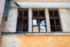 Broken windows with wooden frames in an abandoned yellow building close Stock Photography
