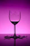 Broken wine glass. On pink/purple background stock image