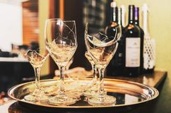 Broken wine glass on a tray with some wine and champagne bottles. Blurred on the background. Broken glass of a party or celebration Stock Image