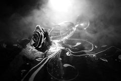 Broken wineglass and wilted rose on dark background. A wilting rose signifies lost love, divorce, or a bad relationship, dead rose. On dark background with stock image