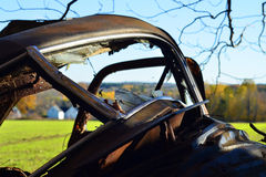 Through the Broken Winshield. An old junk car is abandoned at the edge of a field Stock Photos