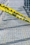Broken wired mesh glass panel with yellow caution tape stretched across in a diagonal fashion. royalty free stock photos