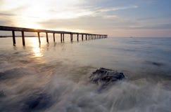 Broken wood bridge and waves crashing on sea at during sunset Royalty Free Stock Image