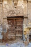 Broken wooden door on grunge stone bricks wall in abandoned street. Broken wooden door on grunge stone bricks wall in abandoned Darb El Labana district, Cairo royalty free stock photo