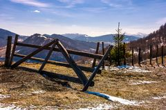 Broken wooden fence on hillside. Springtime is coming. beautiful mountainous landscape with some snow on slopes with weathered grass on a bright day Royalty Free Stock Photo
