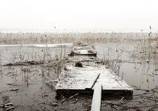 Broken wooden jetty in frozen lake Stock Photo