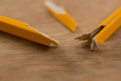 Broken yellow pencil on wooden background Royalty Free Stock Images