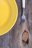 Broken yellow plate - diet. Broken yellow plate and Cutlery on wooden background Royalty Free Stock Photos
