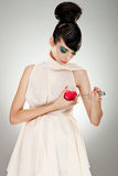 Brokenhearted woman. In fashion dress pointing a big kitchen knife at her heart royalty free stock photography