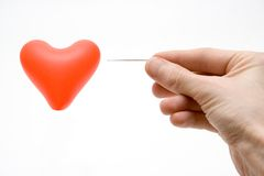 Brokenned heart. Hand with needle pierces air ball Stock Image