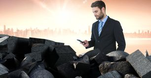Brokenstone bricks pile and businessman on phone in cityscape. Digital composite of Brokenstone bricks pile and businessman on phone in cityscape Royalty Free Stock Photography