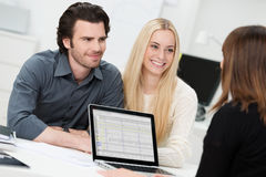 Broker or adviser with a young couple Stock Photos