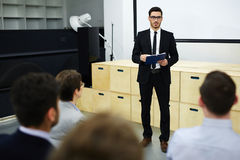 Broker briefing. Confident men in suit making business report to his colleagues royalty free stock photo