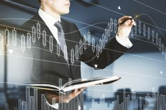 Broker concept. Side view of handsome businessman with document in hands drawing abstract forex chart in blurry interior with sunlight. Broker concept. Double Royalty Free Stock Photo