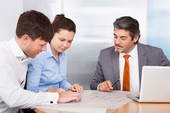 Broker explaining to young couple Stock Photos