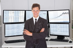 Broker Standing Arms Crossed Against Multiple Screens Royalty Free Stock Photo