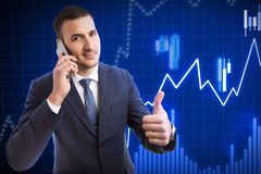 Broker at stock market showing thumb up talking on phone. Male broker working at business stock market showing thumb up as like gesture while talking on the stock photo