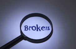 Brokers. Inscription word magnified under a magnifying glass Stock Photos