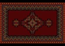 Brokig lyxig matta för tappning med den etniska prydnaden på ett rödbrunt fält Arkivfoto