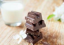 Brokken van donkere chocolade in een glas melk op de raad Royalty-vrije Stock Afbeelding
