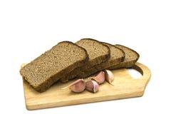 Brokken van zwart brood en knoflook. Stock Foto
