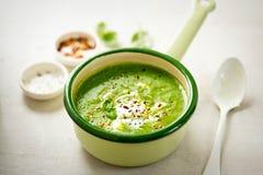 Brokkolispinatserbsen-Cremesuppe mit Sahne und Paprikaflocken Lizenzfreie Stockfotos