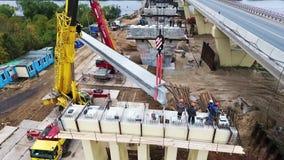 Brokonstruktion på zonen med kranar och arbetande män på stor konkret beem lager videofilmer