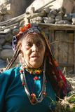 Brokpa / Drokpa elderly woman in Dha, India. Portrait of elderly woman belonging to Drokpa or Brokpa tribe in traditional head covering and jewellery, Dha Royalty Free Stock Images