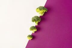 Brokuły na barwionym fiołkowym białym tle przekątna Sezonowi warzywa w nowożytnym stylowym projekta wzorze Obraz Stock