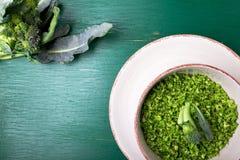Brokuły ryżowi w pucharze na zielonym tle Odgórny widok overhead kosmos kopii Tarci brokuły fotografia stock