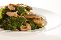 Brokuły smażeni z bekonem, cebulą i pieczarkami w bielu talerzu, Fotografia Royalty Free