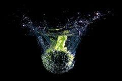 Brokuły spada w wodę, odosobnioną przeciw czarnemu tłu Obrazy Stock