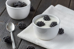 Brombeeren im weißen Jogurt auf weißen Servietten Lizenzfreies Stockfoto