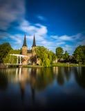 Bron är delen av Oospoorten 1514 och det van vid slutet porten Nederländsk kanal Royaltyfri Foto