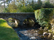 Bron över den berömda Glendalough kloster- platsen med dess runda torn och kyrkogård i de Wicklow bergen i ståndsmässiga Wicklow, Royaltyfria Foton